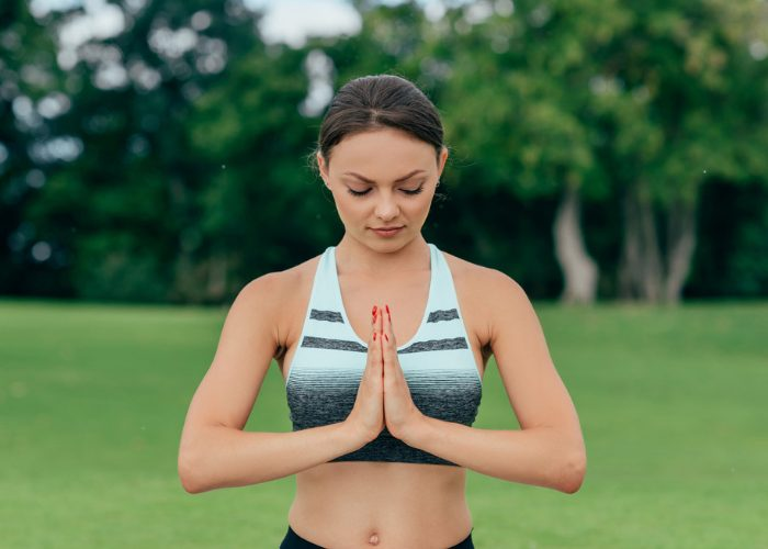 Woman standing with palms touching in prayer position, outdoors in a park doing ujjayi pranayama breathing