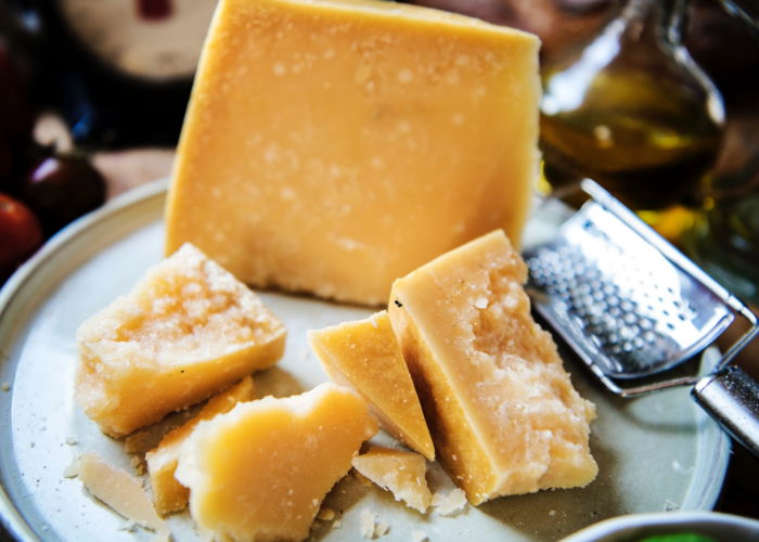 Block of cheese rich in the amino acid valine, laid out on a plate with a cheese grater on the side