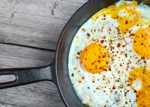 A pan of fried eggs topped with paprika