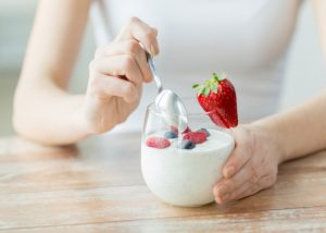 Woman eating yogurt topped with berries in a clear glass
