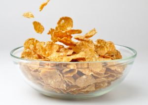 Corn flakes cereal in a clear glass bowl