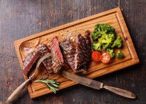 Vitamin B12-rich steak on a wooden board with broccoli and cherry tomatoes on the side