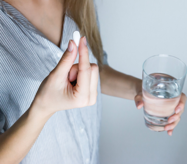 Woman holding onto a glass of water in one hand and a pill in the other