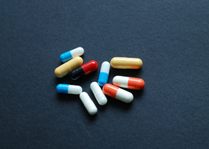 A scattering of colorful pills on a dark blue background