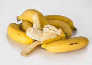 A peeled banana in a pile of whole bananas on a white table