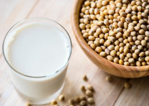 A glass of fortified soy milk next to a wooden bowl full of soy beans