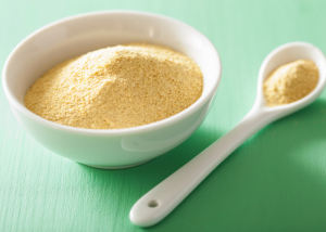 bowl and spoon full of nutritional yeast on a green table