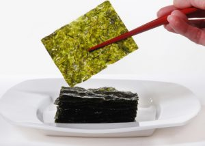 Woman lifting up a thin sheet of dried green seaweed from a pile of it on a white plate