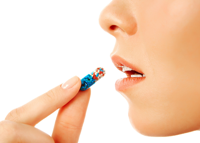 Closeup of woman putting a vitamin pill in her mouth