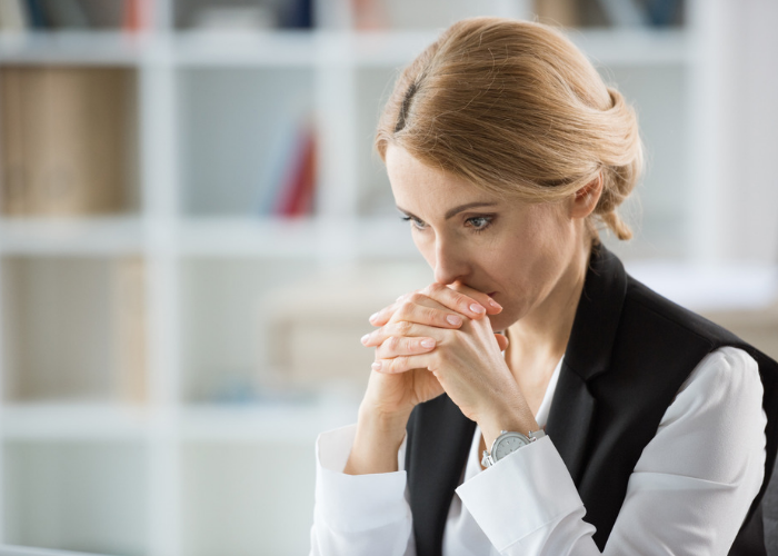 Middle-aged woman looking pensively ahead in concentration with her hands clasped