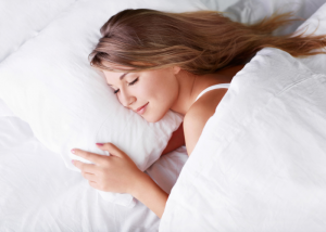 Woman smiling and sleeping soundly under her weighted blanket
