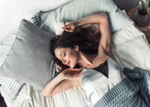 Woman smiling and giving herself a good arm stretch in bed as she wakes up
