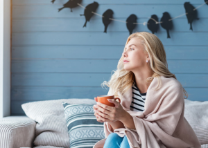 Woman sitting on her couch holding a cup of tea with a blanket draped over her shoulders