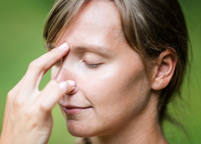 Woman with eyes closed doing breathing exercises