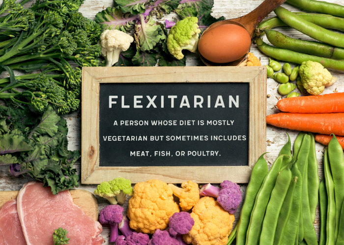 A blackboard with the definition of a flexitarian, surrounded mostly by fresh fruits and vegetables and only a small portion of chicken breast and eggs