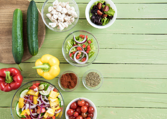 Different plant-based foods laid out on a green wooden table