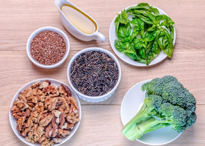 Flatlay of plant-based ingredients such as grains, olive oil, walnuts, broccoli, and green vegetables on a wooden table