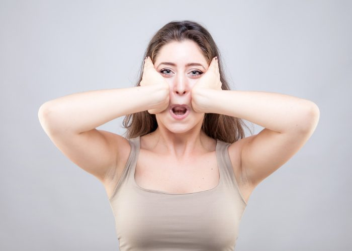 Woman doing face yoga exercises, stretching her face with her two hands and putting her lips inwards