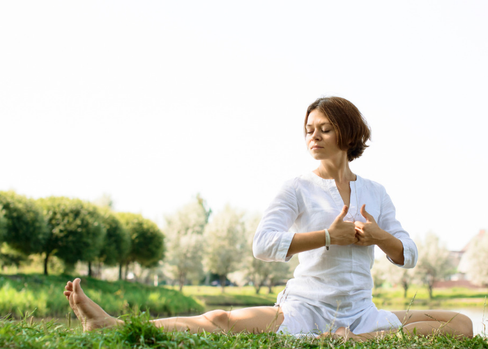 Woman in white Kundalini yoga clothes sitting on the grass in a park practicing a Kundalini yoga pose