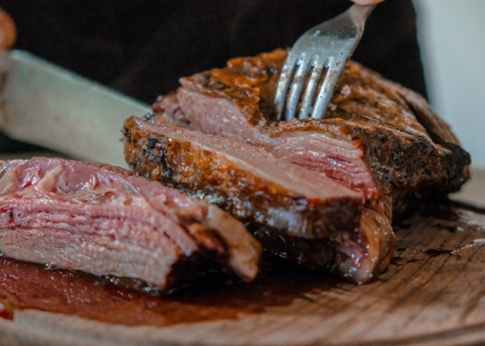 Close up of someone cutting into a juicy steak on a wooden board with a fork and knife