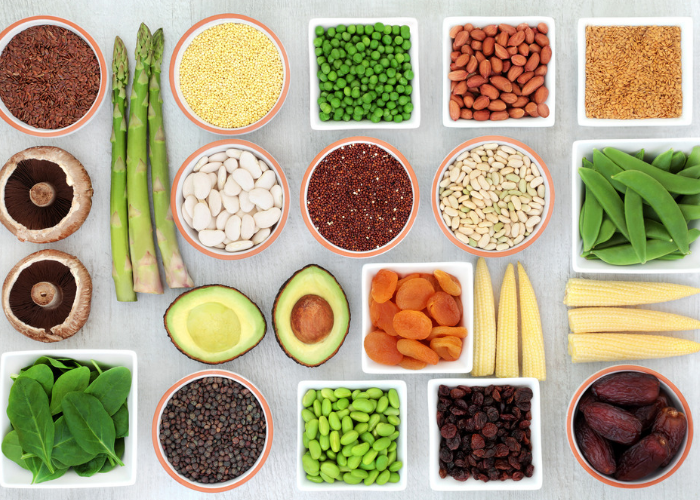 Top down view of flexitarian-friendly foods such as vegetables, seeds and nuts laid out neatly in small bowls on a grey table