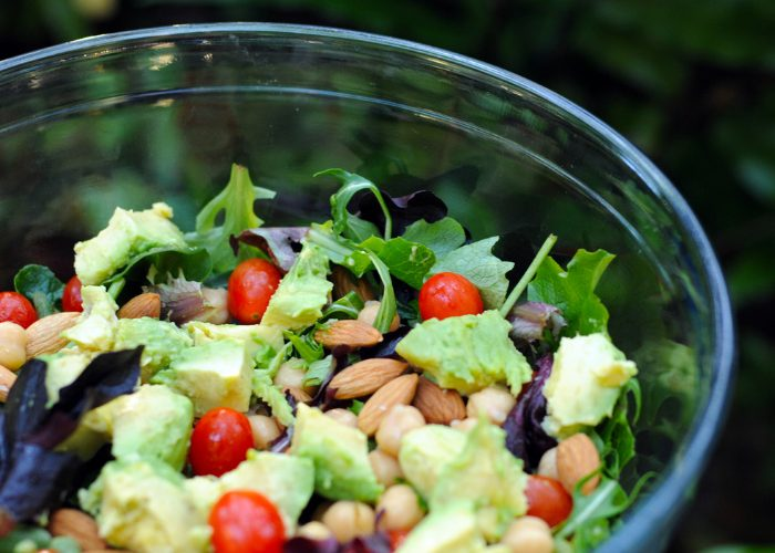 A mixed salad of green vegetables, cherry tomatoes, avocado, almonds, and chickpeas in a glass salad bowl
