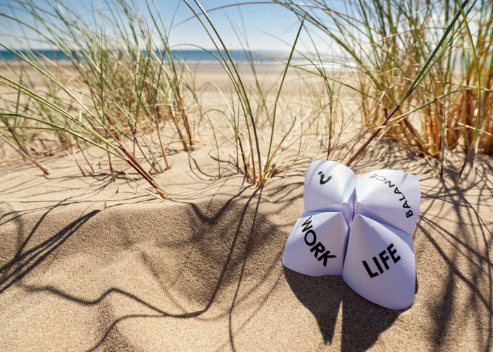 Work, Life, Balance, ?, written on  four separate quadrants of a chatterbox paper on a sandy beach