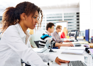 Young woman working at her computer in an office with other colleagues in the background
