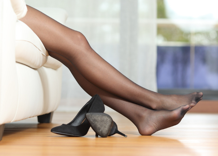 Woman wearing black stockings stretching her legs out to relax while sitting on a white couch, with her black heels kicked off on the floor beside her