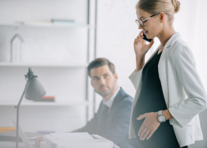A pregnant female office worker on the phone in the office with a male colleague beside her