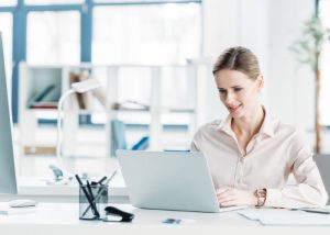 Woman working on her laptop at her desk in her office