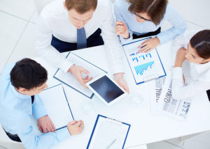 A group of office workers sitting around a table discussing charts and documents laid out on the table
