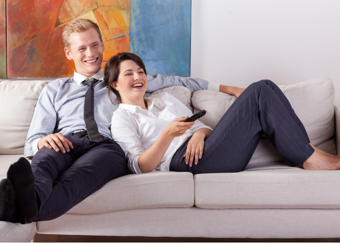 A young heterosexual couple relaxing on the couch after work watching TV