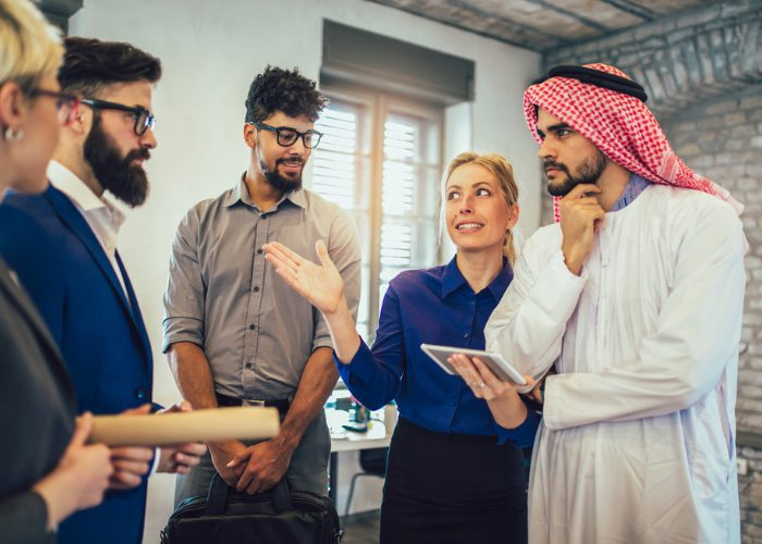 Female Arabic interpreter translating for a group of business men