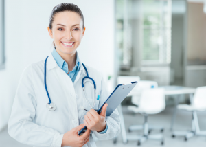 A female doctor with a stethoscope around her neck holding a clipboard and smiling.