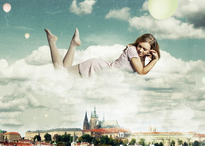 Woman in a dream floating on a cloud above a city
