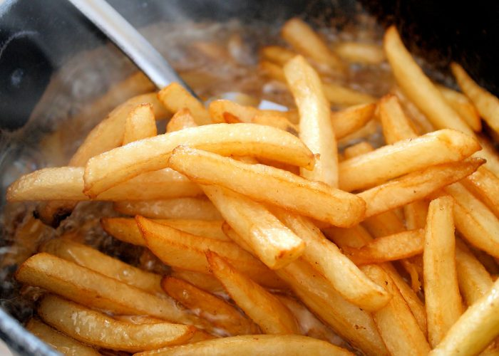 Close up of hot steaming deep fried french fries coming out of the deep fryer