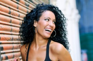 beautiful woman with frizzy dark hair laughing with adult braces