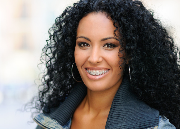 Attractive African American woman smiling with metal adult braces