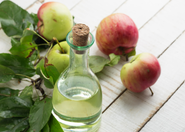 Bottle of apple cider vinegar on a wooden table with fresh apples around it