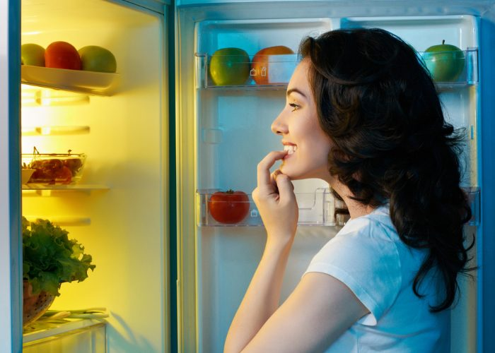 Woman looking into her fridge for food late at night