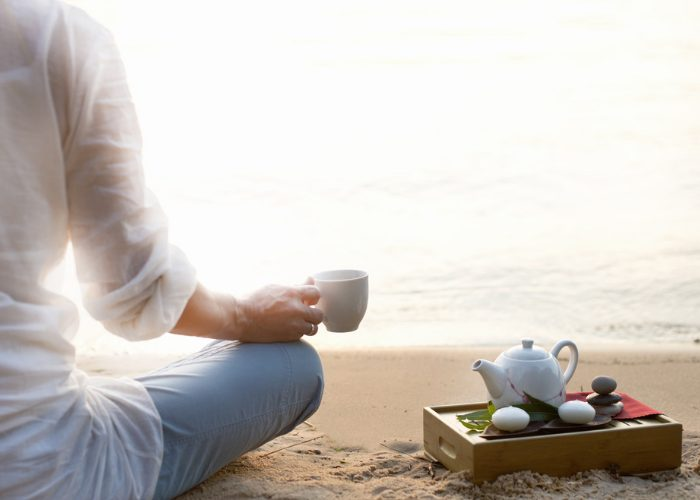 Woman sat on the beach relaxing with a pot of tea and looking out to sea