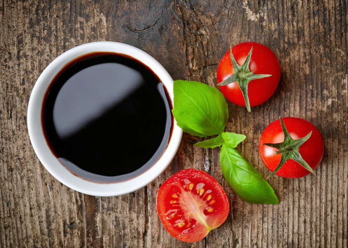 Top down image of a bowl of balsamic vinegar next to fresh cherry tomatoes and a sprig of basil