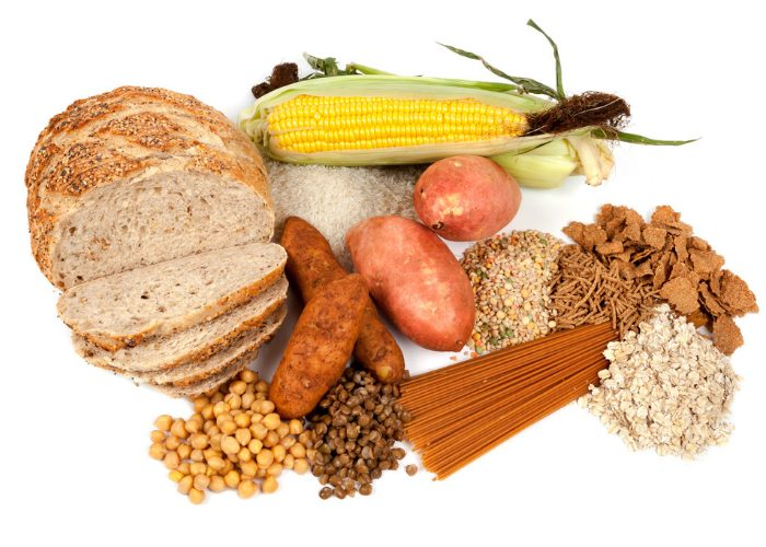 Different complex carb foods like corn, grains, tubers, beans, laid out on a white surface