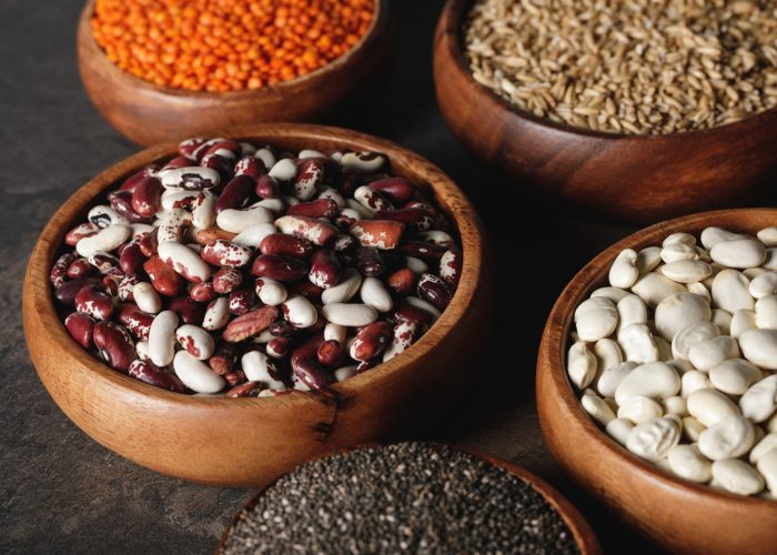 Different beans, lentils and other plant proteins in wooden bowls