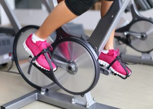 Woman doing cardio exercises on gym exercise bike