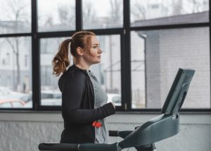 Slightly curvy woman doing cardio training on treadmill