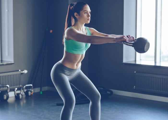 Woman doing kettle bell strength training exercises at the gym