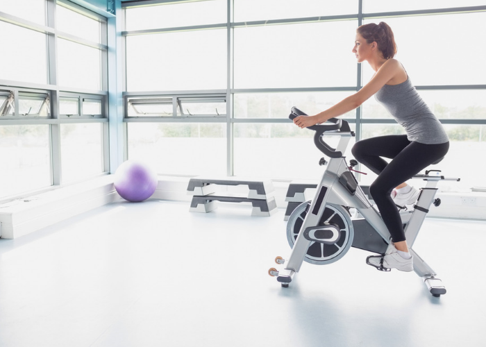 Woman on an exercise bike in a brightly lit gym