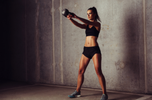 Fit woman with toned abs and legs swinging a kettlebell for strength training